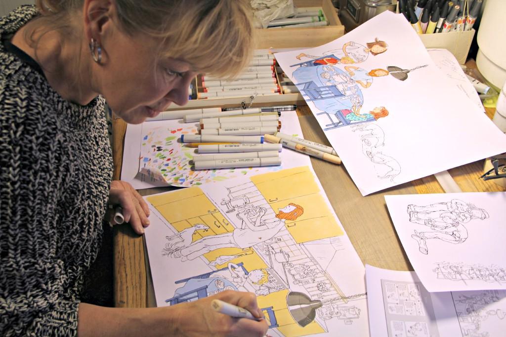 Kuvittaja Christel Rönns Nakki lautasella -kuvituksen parissa.